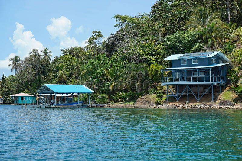 Off grid waterfront home on lush tropical coast stock images
