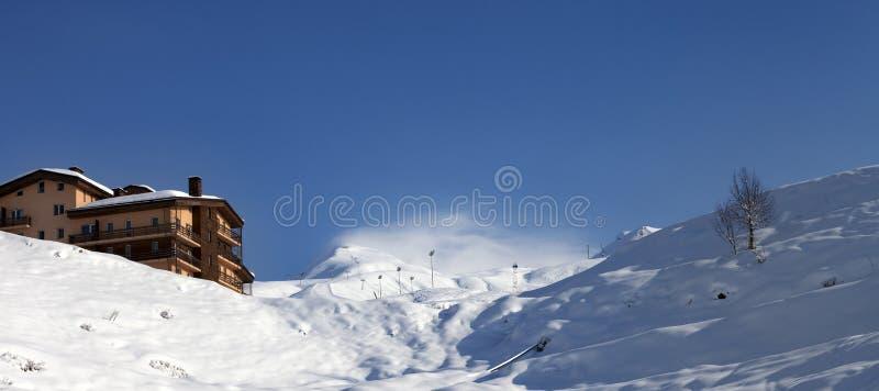 Off-piste κλίση και ξενοδοχείο στα χειμερινά βουνά στοκ εικόνες