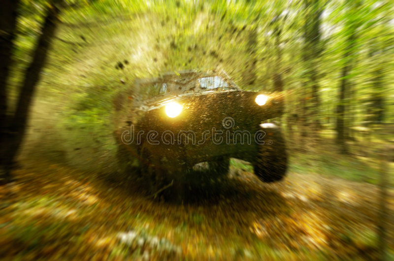 Off-road action. Military off-road vehicle storming through forest, splattering mud - captured in mid-air royalty free stock photo