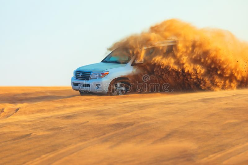 Off-road adventure with SUV in Arabian Desert at sunset. Offroad vehicle bashing through sand dunes in Dubai desert. Dune bashing royalty free stock image