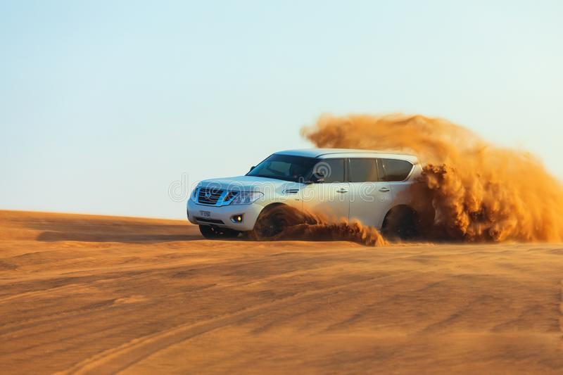 Off-road adventure with SUV in Arabian Desert at sunset. Offroad vehicle bashing through sand dunes in Dubai desert. Dune bashing stock photo