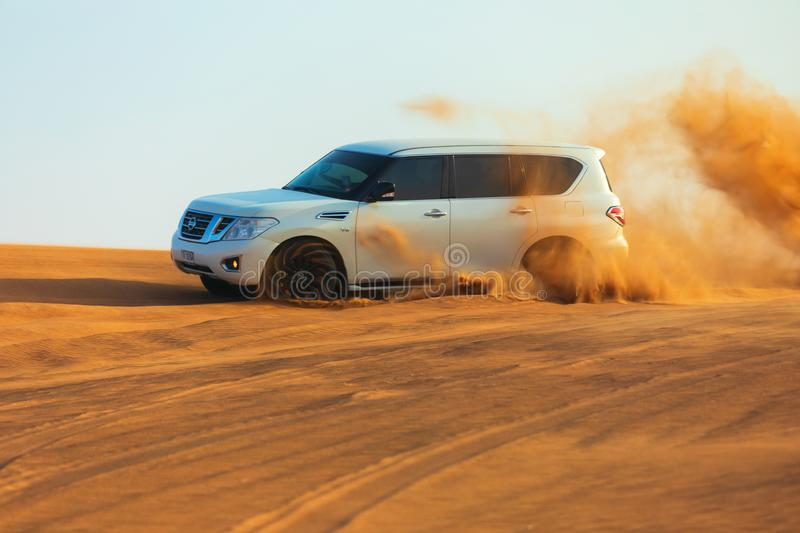 Off-road adventure with SUV in Arabian Desert at sunset. Offroad vehicle bashing through sand dunes in Dubai desert. Dune bashing royalty free stock images