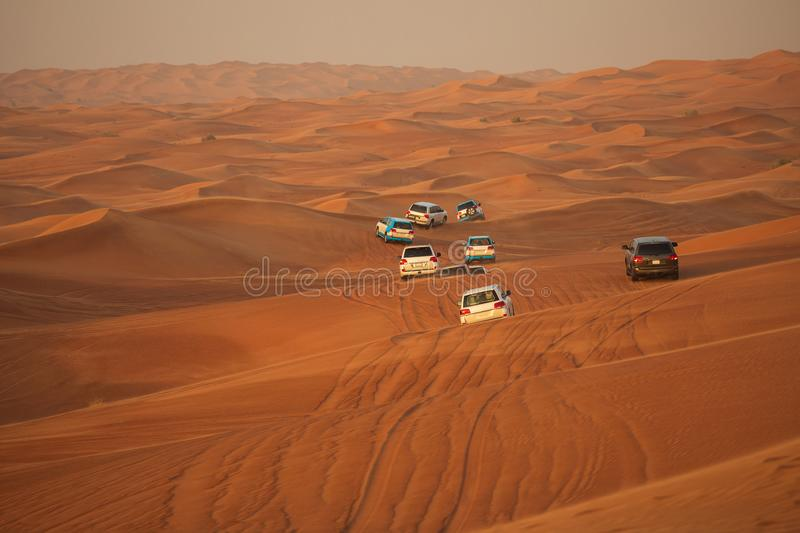 Off-road adventure with SUV driving in Arabian Desert at sunset. Offroad vehicle bashing through sand dunes in Dubai desert. Off-road safari adventure with SUV stock photography