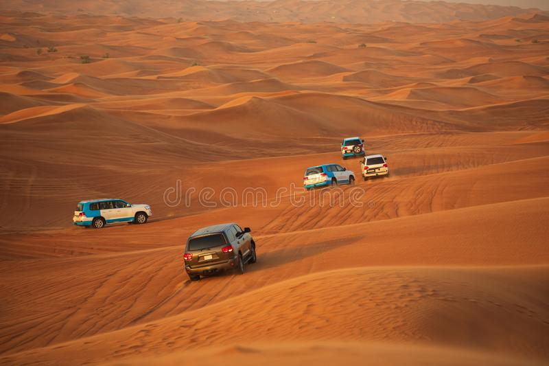 Off-road adventure with SUVs driving in Arabian Desert at sunset. Traditional entertainment for tourists with vehicle bashing. Off-road safari adventure with stock photo