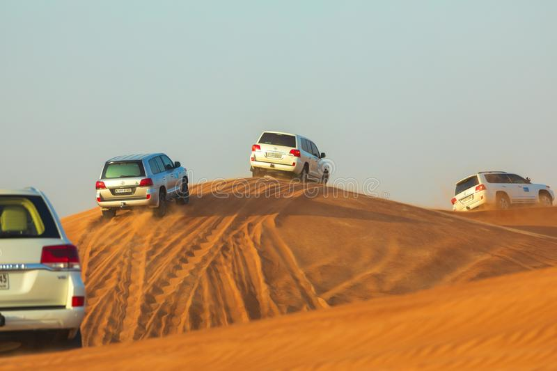 Off-road adventure with SUVs driving in Arabian Desert at sunset. Traditional entertainment for tourists with vehicle bashing thro. Ugh sand dunes in Dubai royalty free stock photo
