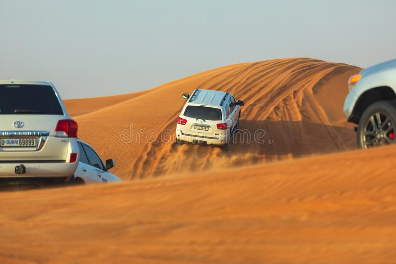 Off-road adventure with SUVs driving in Arabian Desert at sunset. Traditional entertainment for tourists with vehicle bashing thro. Ugh sand dunes in Dubai stock photos