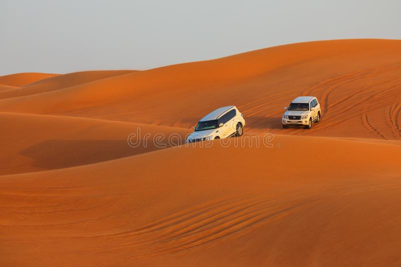 Off-road adventure with SUVs driving in Arabian Desert at sunset. Traditional entertainment for tourists with vehicle bashing thro. Ugh sand dunes in Dubai stock images