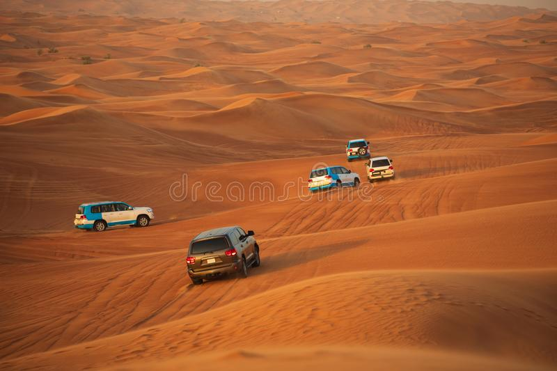 Off-road adventure with SUVs driving in Arabian Desert at sunset. Traditional entertainment for tourists with vehicle bashing thro. Ugh sand dunes in Dubai stock photo
