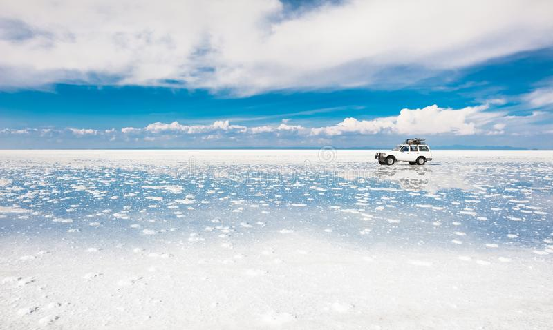 Off-road car driving through Salar de Uyuni salt flat in Bolivia royalty free stock image