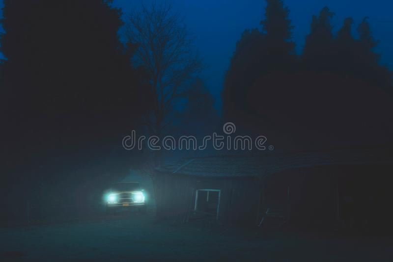 Off road car with headlights on in misty forest near old barn. Off road car with headlights on in misty forest near old barn at dusk royalty free stock photos