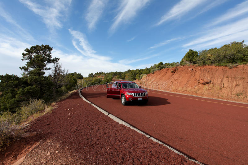 Off road car on red tarmac in high mountains royalty free stock photo
