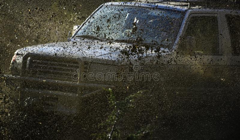 Off road car or sport utility vehicle overcomes obstacles. Auto racing, competition and energy concept Car crossing. Off road car or sport utility vehicle stock image