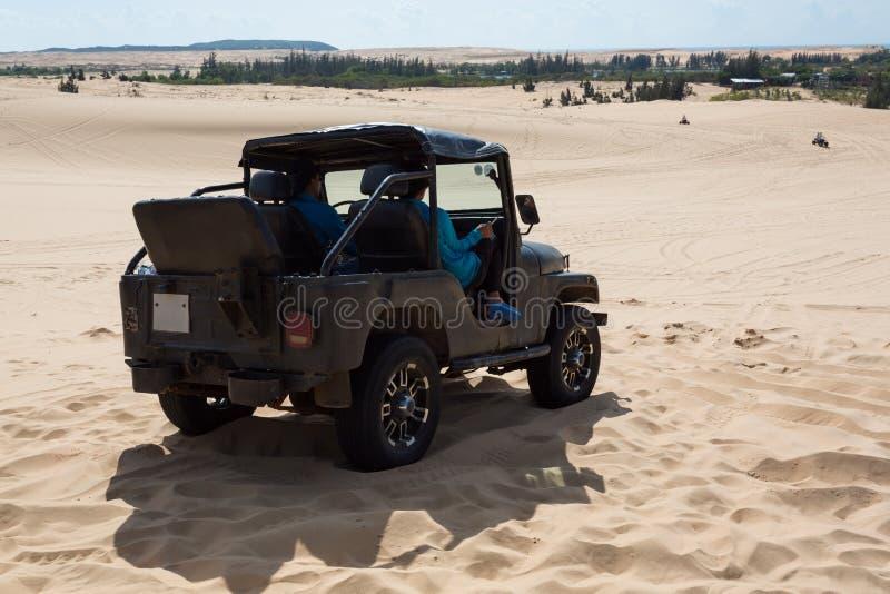 Off road car vehicle in white sand dune desert at Mui Ne stock photo