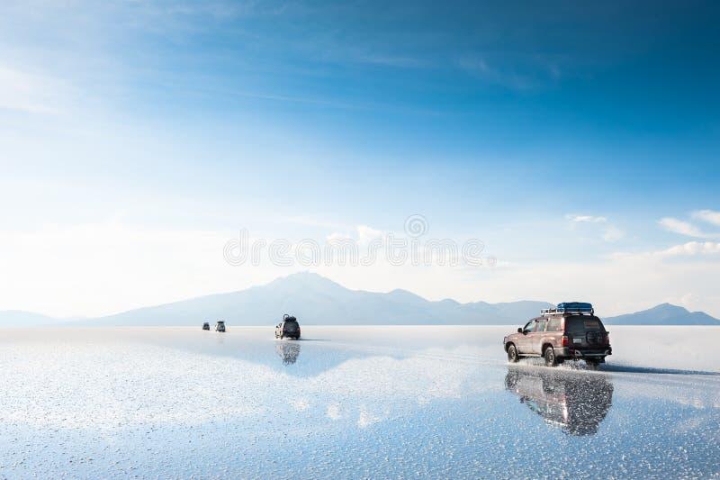 Off-road cars driving through Salar de Uyuni salt flat in Bolivia royalty free stock photo