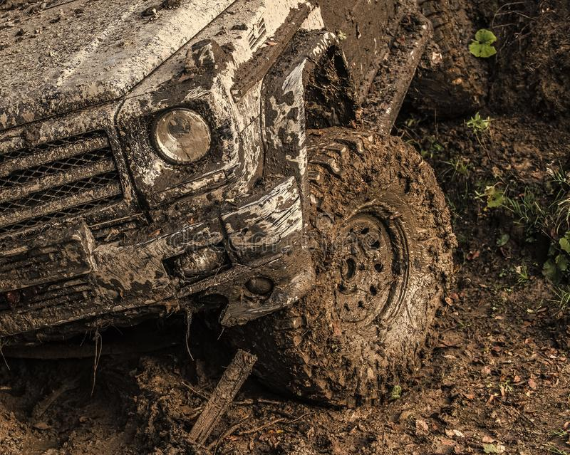 Off-road. Dirty wheel of car after offroad race. SUV in autumn forest, fallen leaves. Car on country road covered with mud. Impassibility of roads concept royalty free stock photo