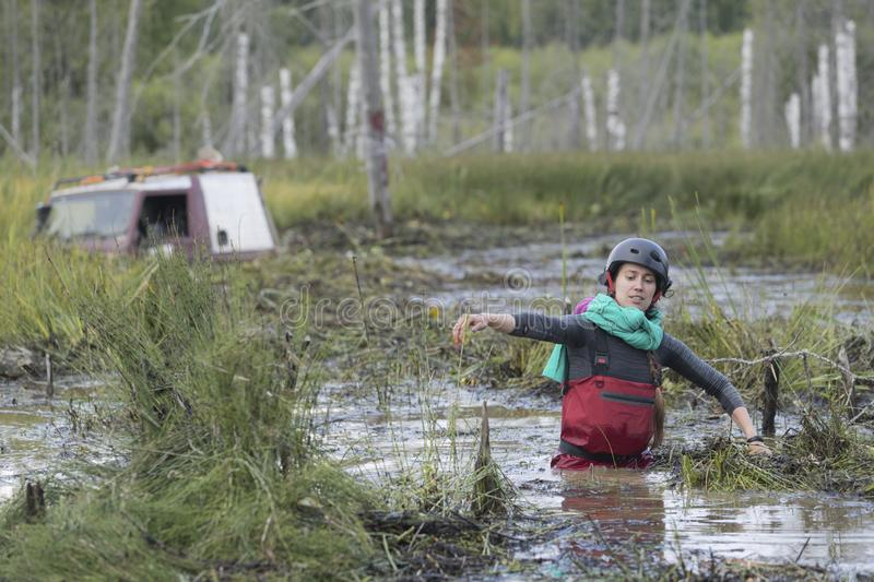 Off road sport, cars overcome the swamp. Girl pilot leaves her SUV stuck in a swamp, natural light, off road stock photo