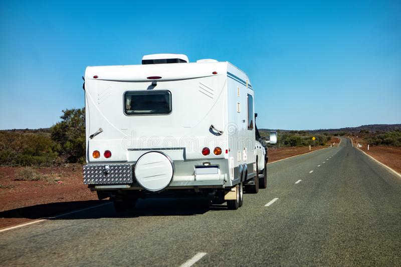 An off-road SUV car towing a caravan in Western Australia. In remote outback landscape with nobody around stock photo