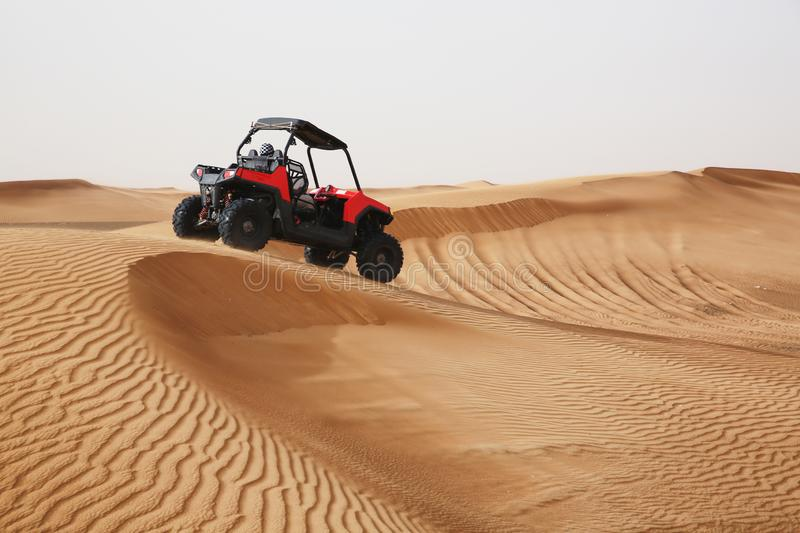 Off-road SUV vehicle speeding through sand dunes in the Arabian royalty free stock images