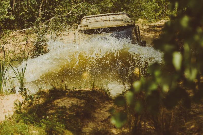 Off-road travel on mountain road. Offroad vehicle coming out of a mud hole hazard. Drag racing car burns rubber. Extreme. Off-road car. Rally racing stock photos
