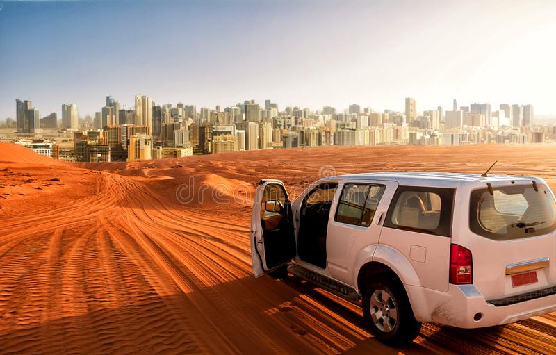 Off-road vehicle on a desert sand track and the city in the background stock image