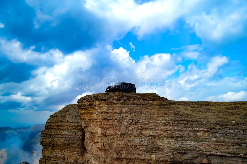 Off-road vehicle on the edge of a rock cliff against the colorful blue sky with clouds. Extreme mountain safari. Bermutyt plateau, Caucasus, car, natural royalty free stock photos