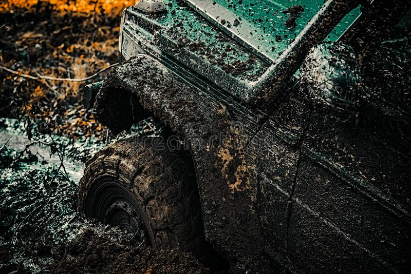 Off-road vehicle goes on the mountain. Bottom view to big offroad car wheel on country road and mountains backdrop. Tracks on a muddy field. Offroad vehicle royalty free stock photos