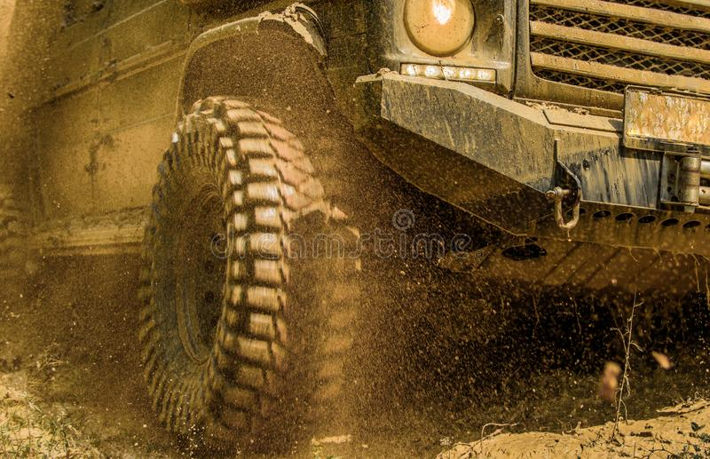 Off-road vehicle goes on mountain way. Bottom view to big offroad car wheel on country road and mountains backdrop. Tires in preparation for race. Road stock images