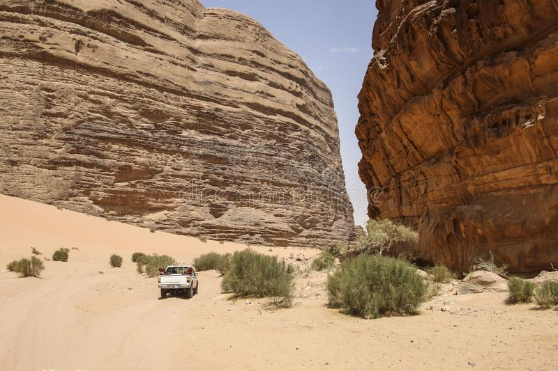 Off-road vehicle for safaris rides through the Red Mountains of. The canyon of Wadi Rum desert in Jordan. Wadi Rum also known as The Valley of the Moon in stock images
