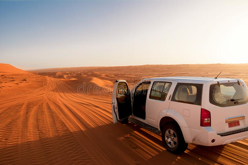 Off-road vehicle in the wahiba sands desert dunes at sunset stock photography