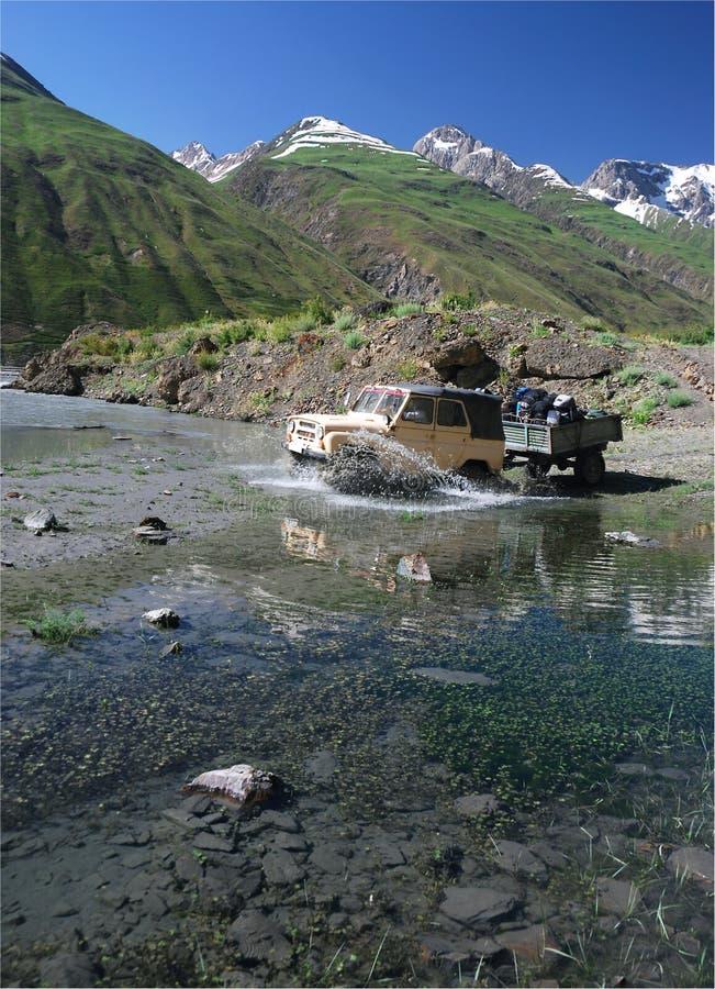 Off-road voertuig dat de rivier kruist stock fotografie
