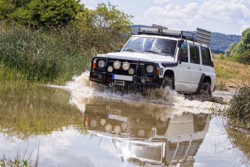 Off-road voertuig die rivier kruisen stock foto's