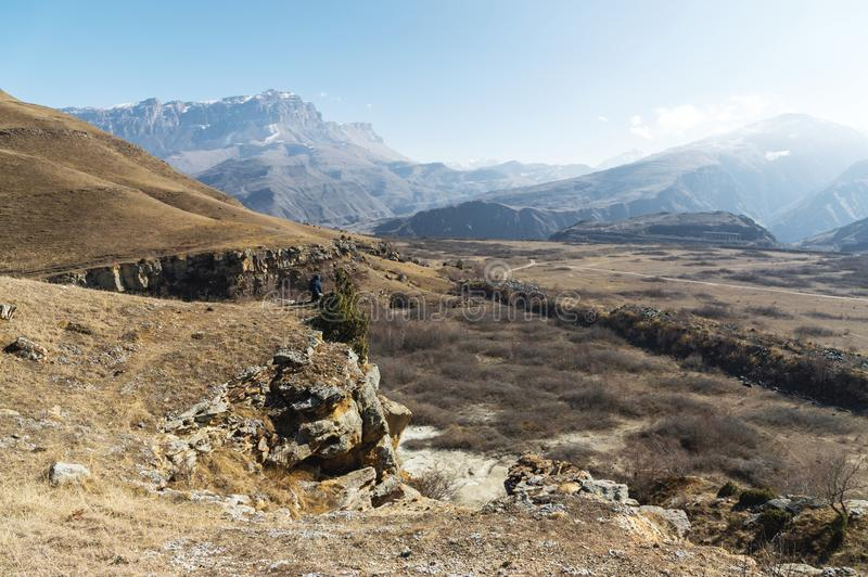 The off-season landscape of the mountains of the Caucasus on a sunny day. a man on the edge of a cliff looking out into. The distance next to a tree standing on stock photo