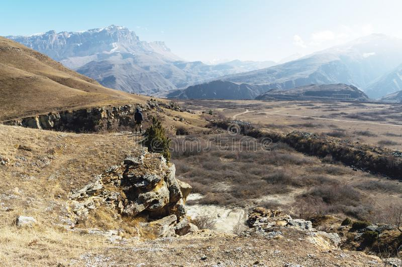 The off-season landscape of the mountains of the Caucasus on a sunny day. a man on the edge of a cliff looking out into. The distance next to a tree standing on royalty free stock photos