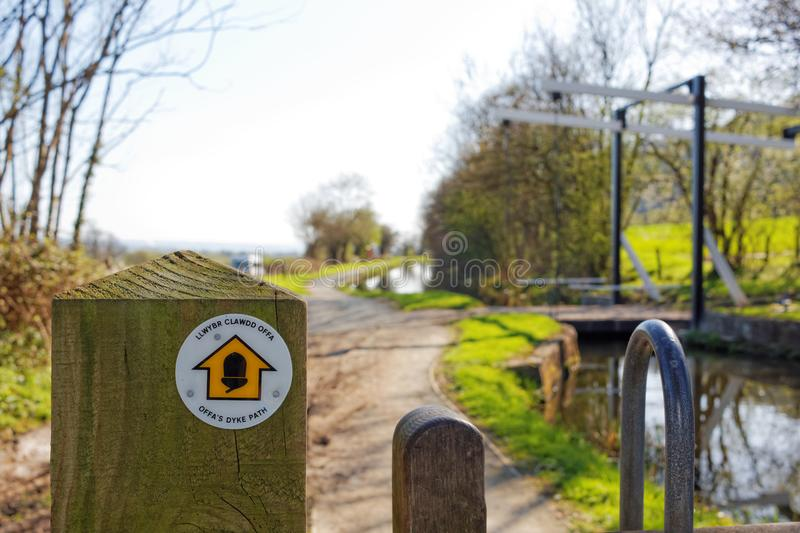 Offa`s Sign Post and Lift Bridge on Montgomery Canal, Powys, Wales. Powys, Wales, April 19, 2018. Editorial photograph of wooden post with route sign near royalty free stock photo
