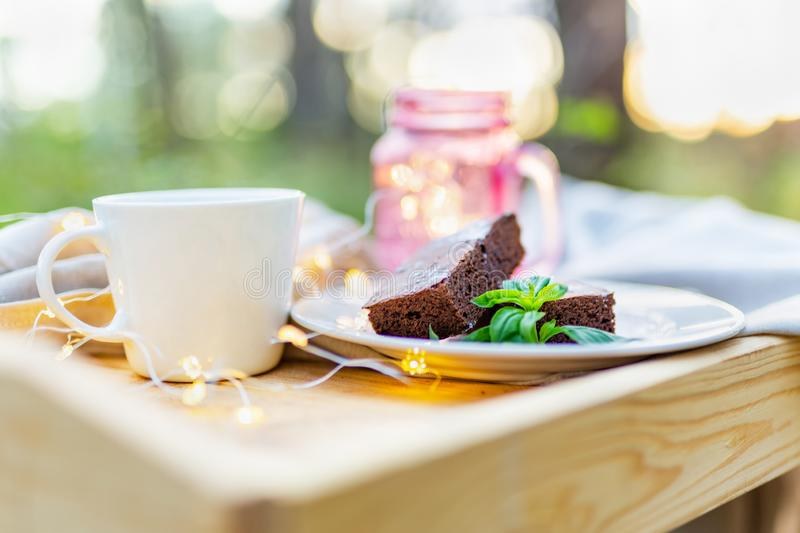 ?offee table served with coffee, sweet brownie cake decorated with some lights royalty free stock image
