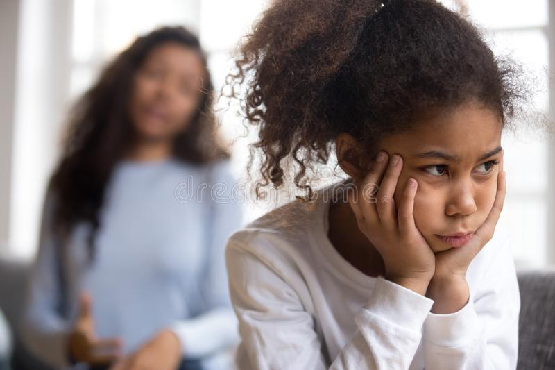 Offended African American preschooler girl looking in distance. Holding head in hands, talking mother on background, family conflict, child punishment royalty free stock photography