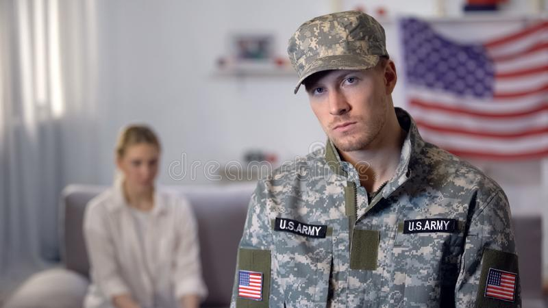 Offended american soldier looking at camera, upset wife sitting on sofa, quarrel. Stock photo stock photos