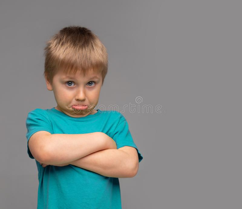 Offended boy in blue t-shirt. Sad and upset kid in studio. Childhood concept. stock photography