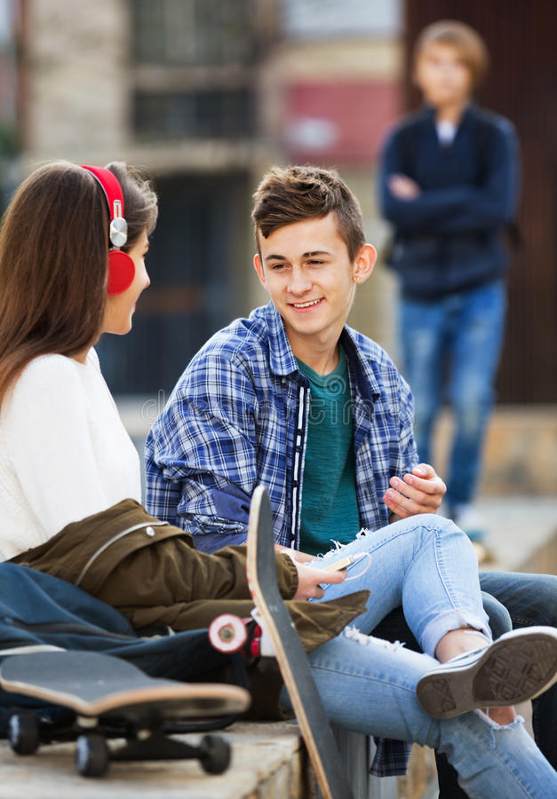 Offended boy and couple of teens apart on the street stock photos
