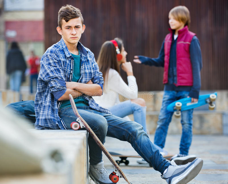 Offended boy and couple of teens apart on the street stock images