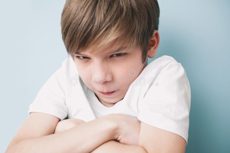 Offended boy folded his arms and looked angrily at camera. Emotion concept stock photo