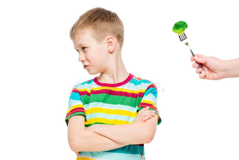 Offended displeased boy refuses serving of healthy broccoli. Portrait is isolated royalty free stock photos