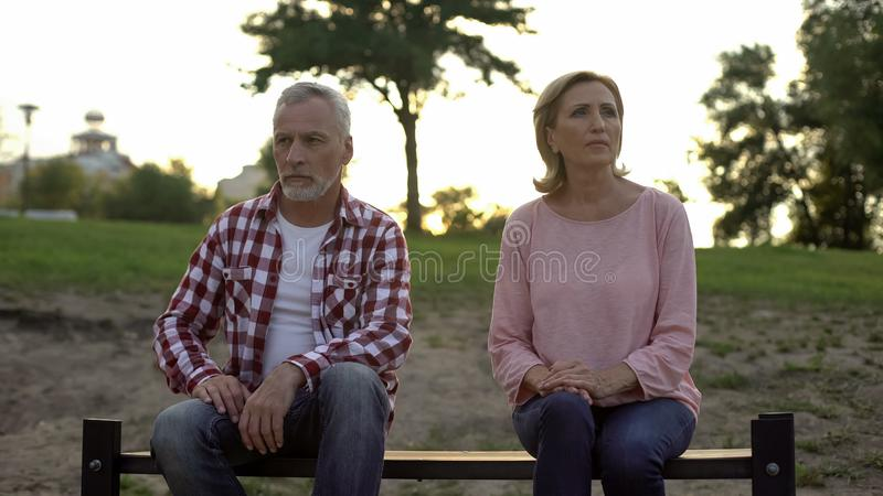 Offended elderly couple sitting on bench and thinking about divorce, relations royalty free stock images
