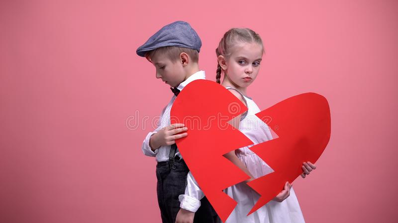 Offended kids couple holding broken pieces of red heart, quarrelling, brake up royalty free stock photo