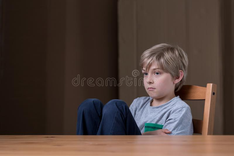 Offended little child. Sitting at the desk royalty free stock photos