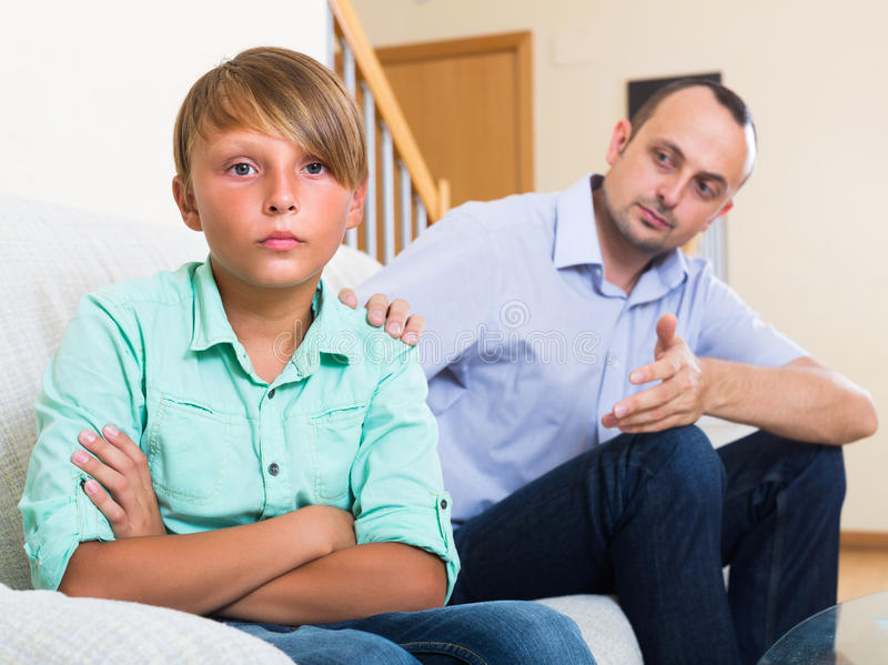 Offended man and stubborn teenager. Offended men trying to reconcile with stubborn teenager after quarrel stock photos