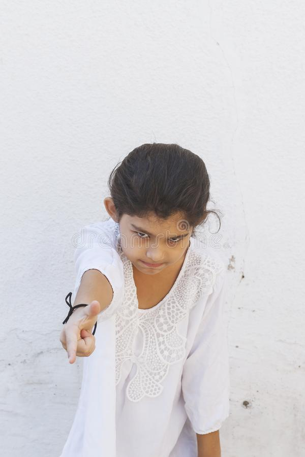 He Offended Me. School girl saying it`s him pointing with her finger. Showing hand gesture this is him, he hurt me. Negative emotions. The upset girl points to royalty free stock images