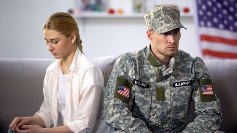 Offended military officer and girlfriend sitting on sofa, relationship problems. Stock photo stock image