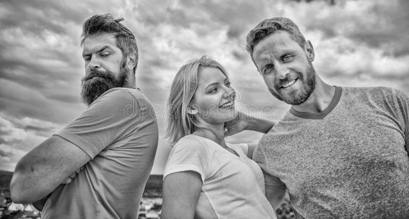 Offended partner still suffers. Girl stand between two men. What do when you feel rejected. Couple and rejected partner stock photos