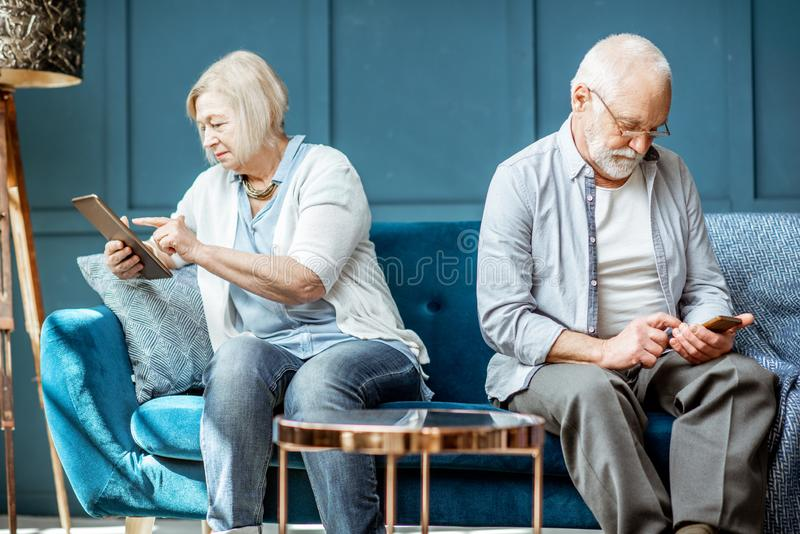 Offended senior couple on the couch at home stock photo